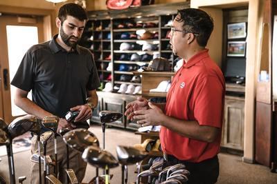 Sprzedawca kijów golfowych rozmawia z klientem